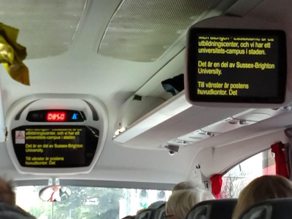 Skrivtolkning visas på TV-skärmar inuti en buss.